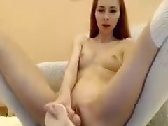 Slim redhead shoves toy in her two holes